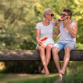 Couple mangeant une pastèque sur une branche en été