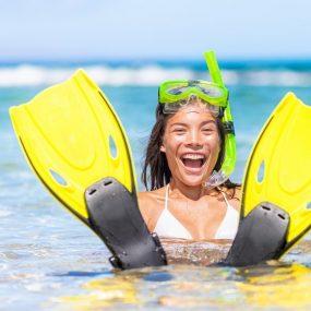 femme avec des palmes dans l'eau sur la plage